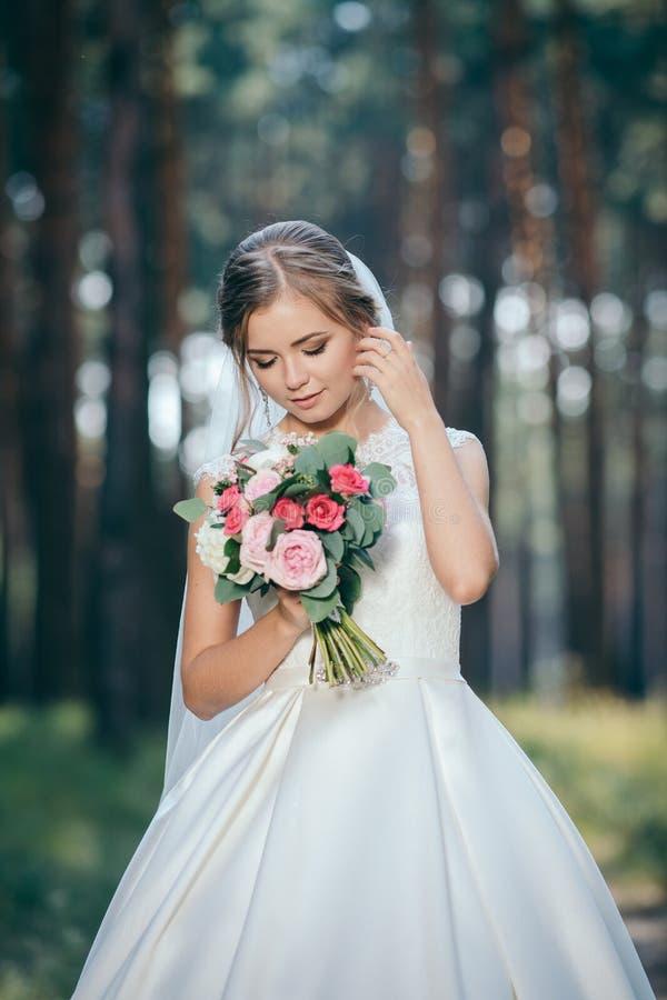 Een mooi bruidportret in het bos de overweldigende jonge bruid is ongelooflijk gelukkig De dag van het huwelijk stock foto's