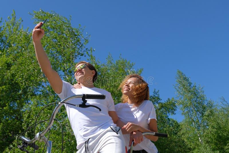 Een mooi donker-gevild meisje en een Europees-Kijkt kerel op een fiets, gekleed in witte T-shirts die Selfie fotograferen stock foto's