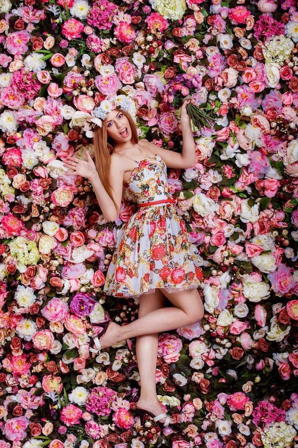 Een mooi emotioneel meisje met bloemenboeket dichtbij een bloemenwa stock afbeelding