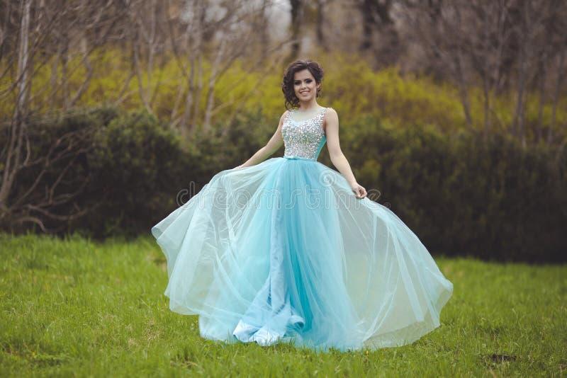 Een mooi gediplomeerd meisje spint in een opheldering in een blauwe kleding Elegante jonge vrouw in een mooie kleding in royalty-vrije stock foto