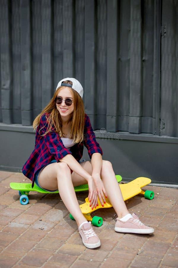 Een mooi glimlachend blond meisje die zonnebril, geruite overhemd en denimborrels dragen is op heldere logboards aanwezig stock foto's