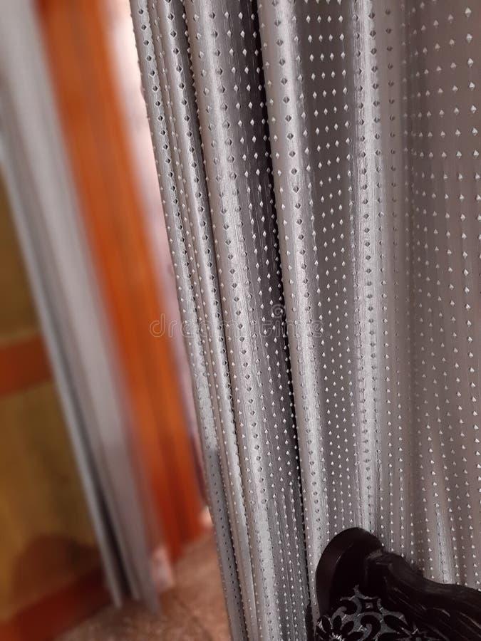 Een mooi grijs gordijn met stippen stock foto's