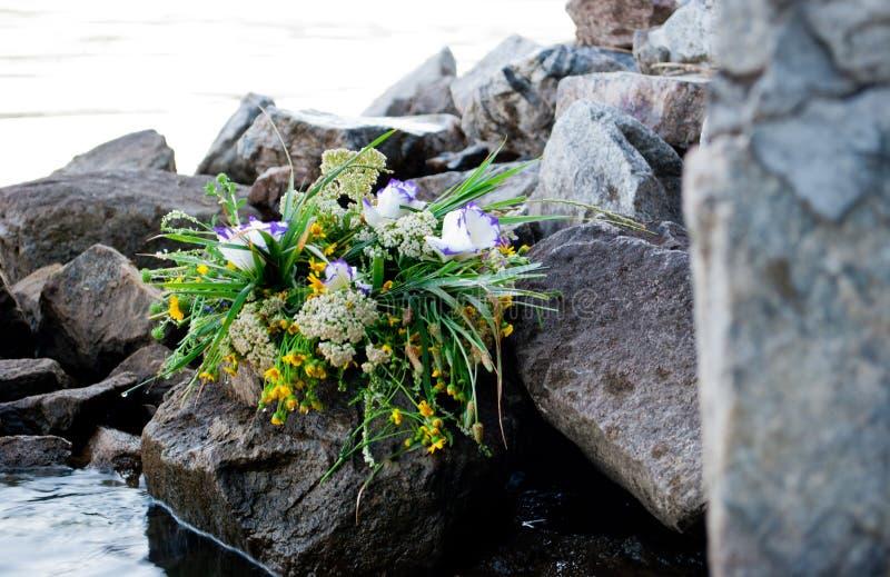 Een mooi groot boeket van bloemenkroon ligt op de stenen op de achtergrond van de rivier Ivan Kupala royalty-vrije stock afbeeldingen