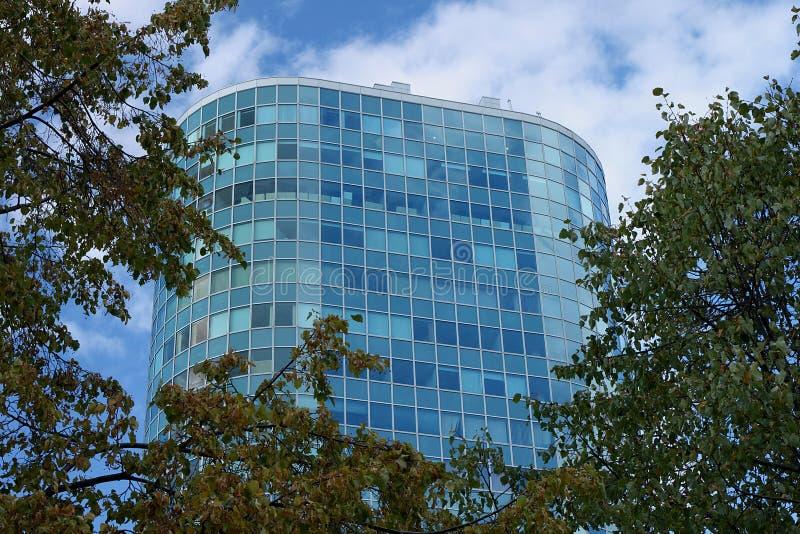 Een mooi hoog blauw gebouw van het glasbureau dat door bomen wordt omringd stock foto's