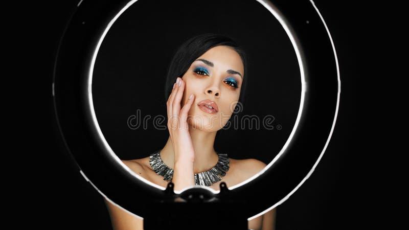 Een mooi jong Kaukasisch meisje met een mooie samenstelling kijkt uit van achter een cirkellamp voor portretfoto het schieten stock foto