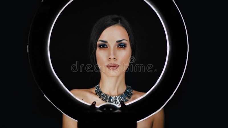 Een mooi jong Kaukasisch meisje met een mooie samenstelling kijkt uit van achter een cirkellamp voor portretfoto het schieten royalty-vrije stock foto's