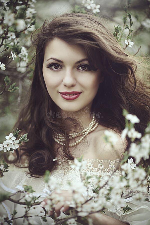 Een mooi jong meisje bevindt zich onder de bloeiende bomen Witte bloemen De lente Een meisje met haar haar in een witte kleding stock afbeelding