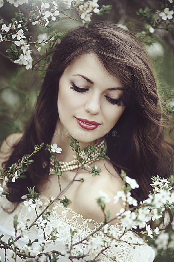 Een mooi jong meisje bevindt zich onder de bloeiende bomen Witte bloemen De lente Een meisje met haar haar in een witte kleding royalty-vrije stock afbeelding