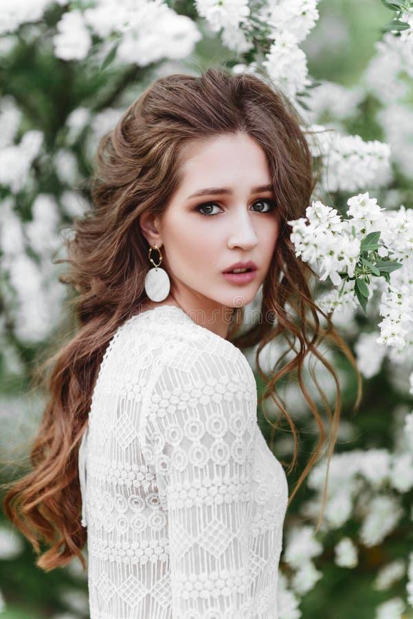 Een mooi jong meisje bevindt zich onder de bloeiende bomen stock afbeeldingen