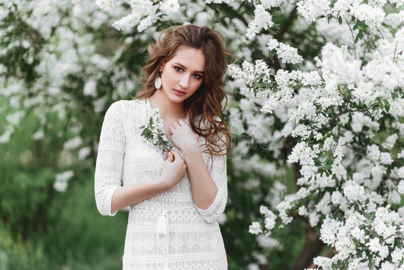 Een mooi jong meisje bevindt zich onder de bloeiende bomen royalty-vrije stock afbeeldingen