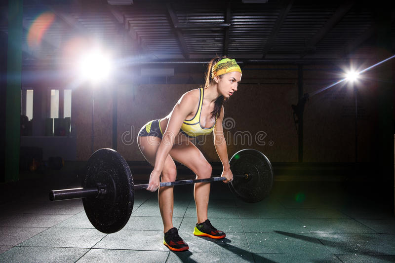 Een mooi jong meisje in de gymnastiek leidt de spieren van de benen op en de rug, deaet oefent deadlift, zit met gewicht, houdt b stock fotografie
