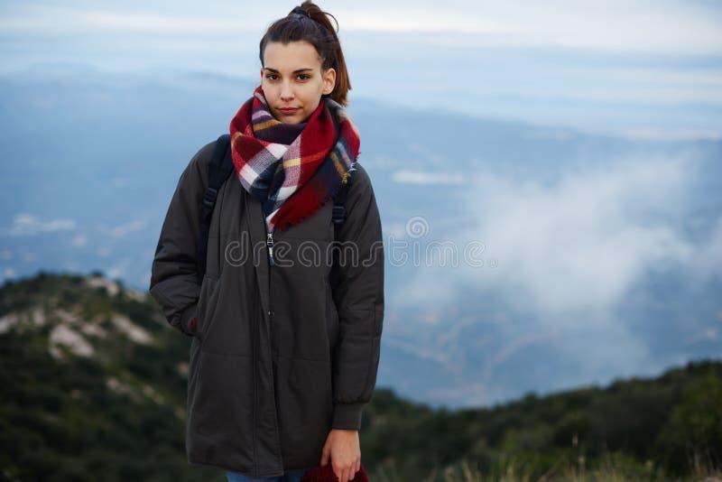 Een mooi jong meisje die zich op die de rand van een klip bevinden in een sjaal wordt verpakt royalty-vrije stock afbeeldingen