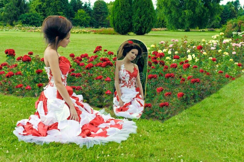 Een mooi jong meisje in een rode kleding kijkt in de spiegel stock foto