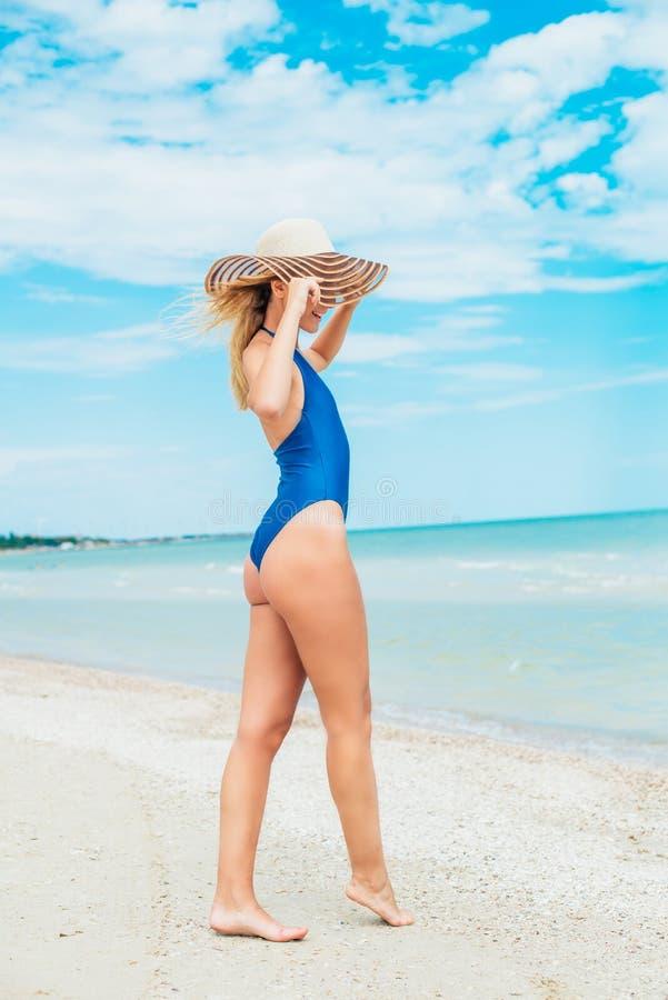 Een mooi jong meisje met blond haar in een blauw zwempak en de hoed ontspannen op strand in het overzees stock foto's