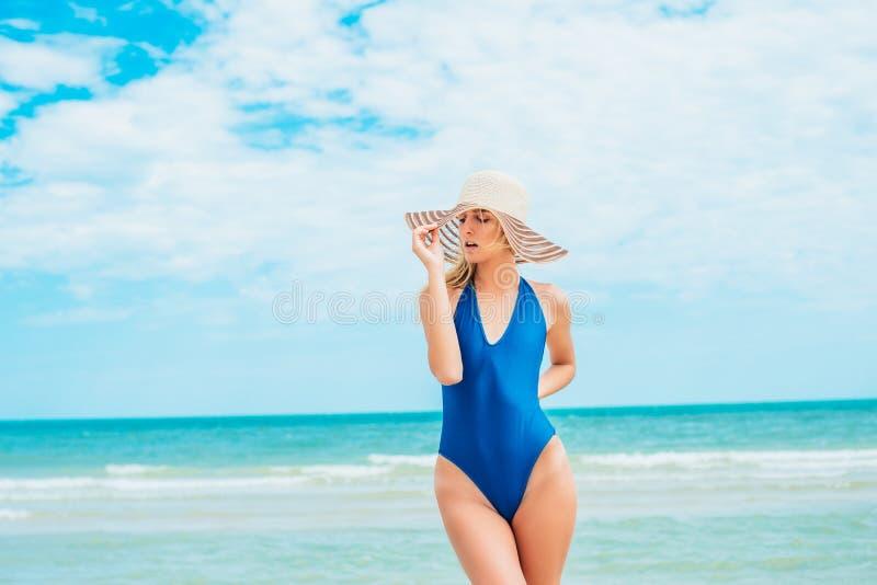 Een mooi jong meisje met blond haar in een blauw zwempak en de hoed ontspannen op strand in het overzees royalty-vrije stock foto