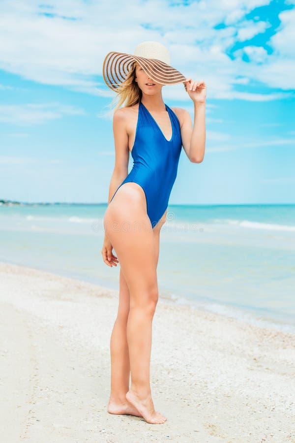 Een mooi jong meisje met blond haar in een blauw zwempak en de hoed ontspannen op strand in het overzees stock afbeelding