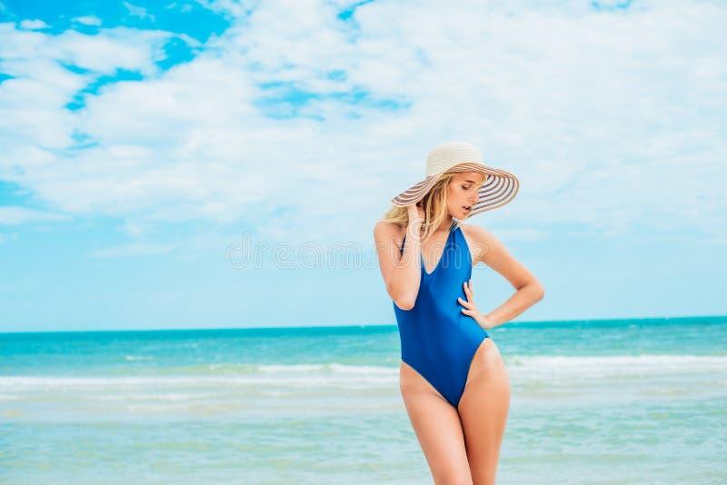 Een mooi jong meisje met blond haar in een blauw zwempak en de hoed ontspannen op strand in het overzees royalty-vrije stock fotografie