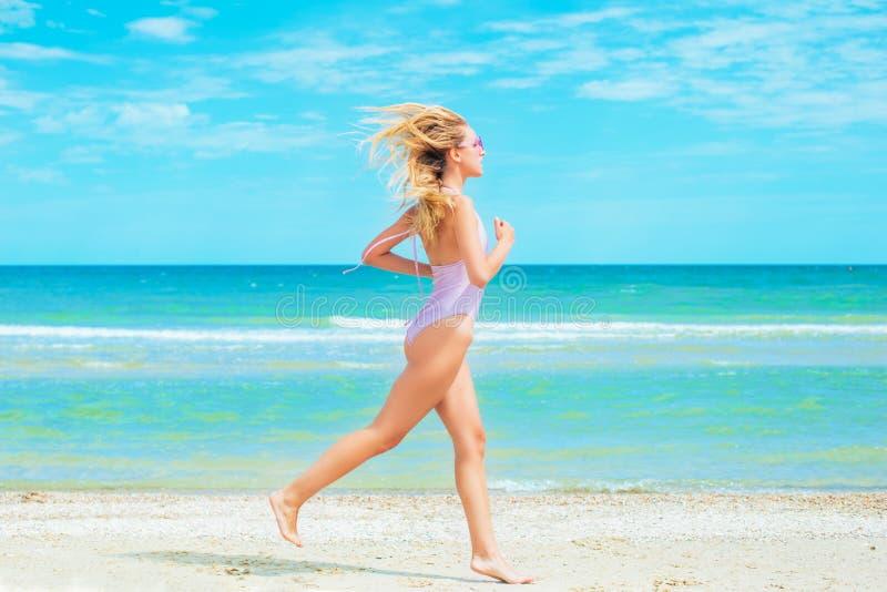 Een mooi jong meisje met blond haar in roze zwempak die op strand in het overzees lopen stock foto's