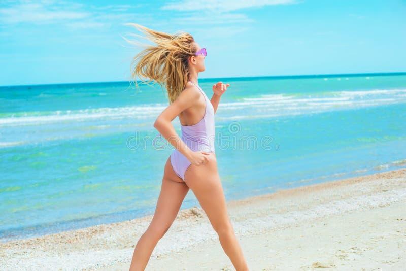 Een mooi jong meisje met blond haar in roze zwempak die op strand in het overzees lopen stock fotografie