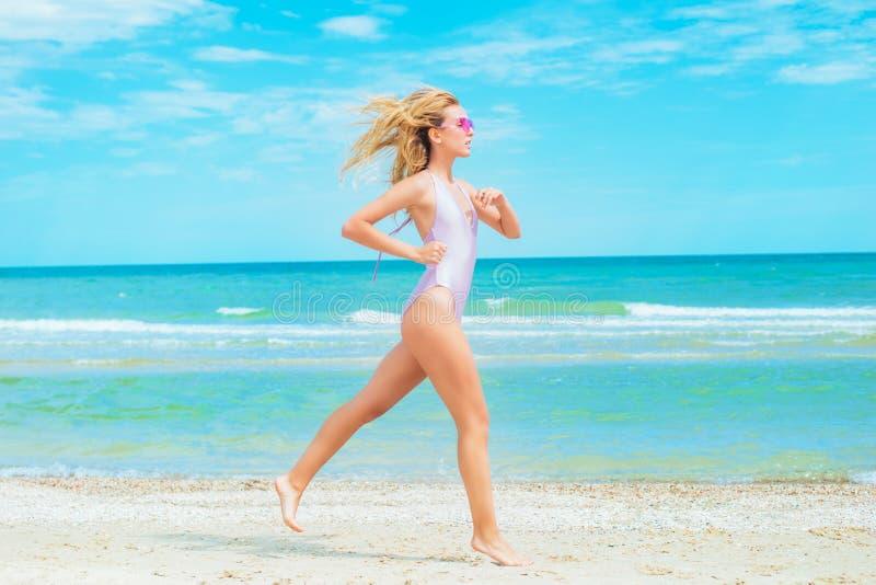 Een mooi jong meisje met blond haar in roze zwempak die op strand in het overzees lopen stock afbeelding