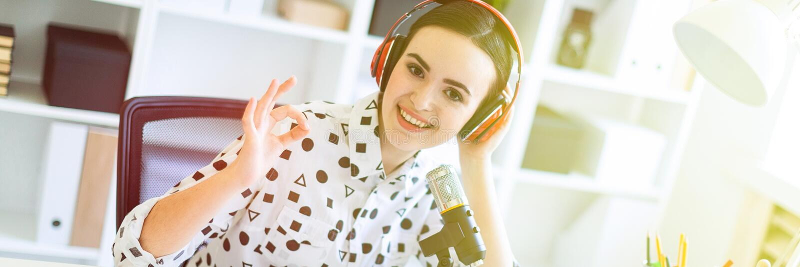 Een mooi jong meisje zit in hoofdtelefoons en met een microfoon bij het bureau in het bureau en toont een teken van o.k. royalty-vrije stock afbeeldingen