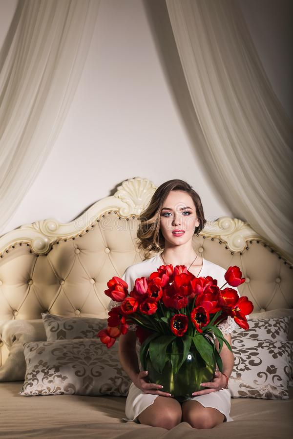 Een mooi jong meisje zit op het bed en houdt heel wat rode tulpen in een vaas 8 maart concept stock foto's