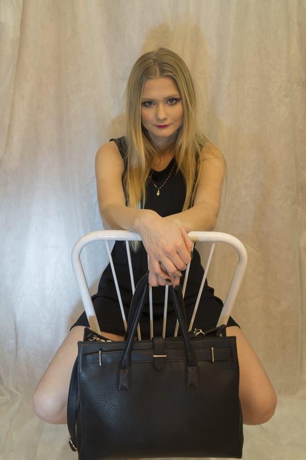 Een mooi jong meisje in een zwarte kleding met het doordringen kijkt zit op een stoel stock fotografie