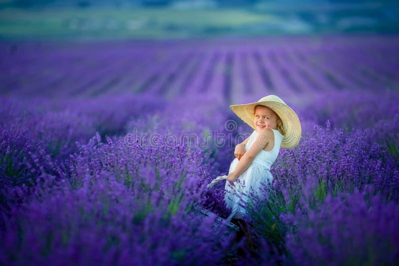 Een Mooi jong meisjes in openlucht portret het jonge geitje in hoed met mand bloeit het oogsten op lavendelgebied de Provence, bi stock foto's