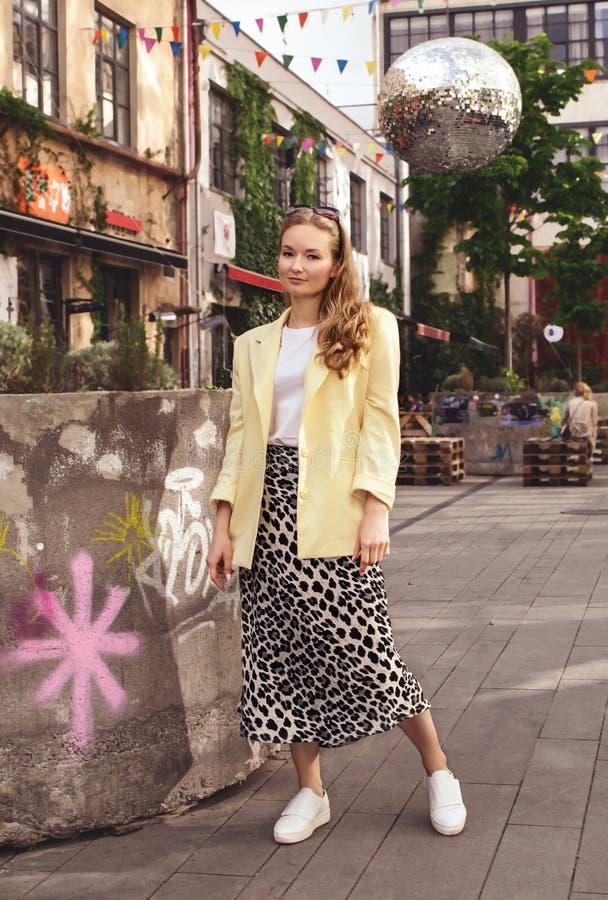 Een mooi jong meisjesblonde in een geel jasje bevindt zich tegen de achtergrond van de stad van Tbilisi georgi? royalty-vrije stock afbeeldingen