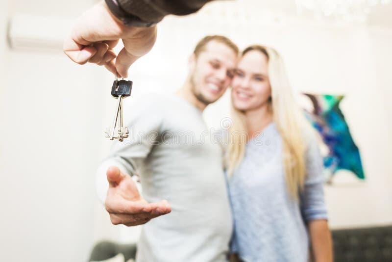 Een mooi jong paar krijgt de sleutels aan hun nieuwe flat van een makelaar in onroerend goed stock foto