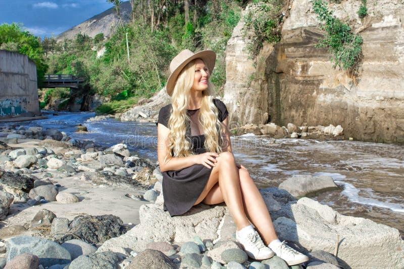Een mooi jong vrouwenblonde met lang haar in een hoedenzitting op een rotsachtige kust door de rivier Rond de bergen en rotsachti royalty-vrije stock foto
