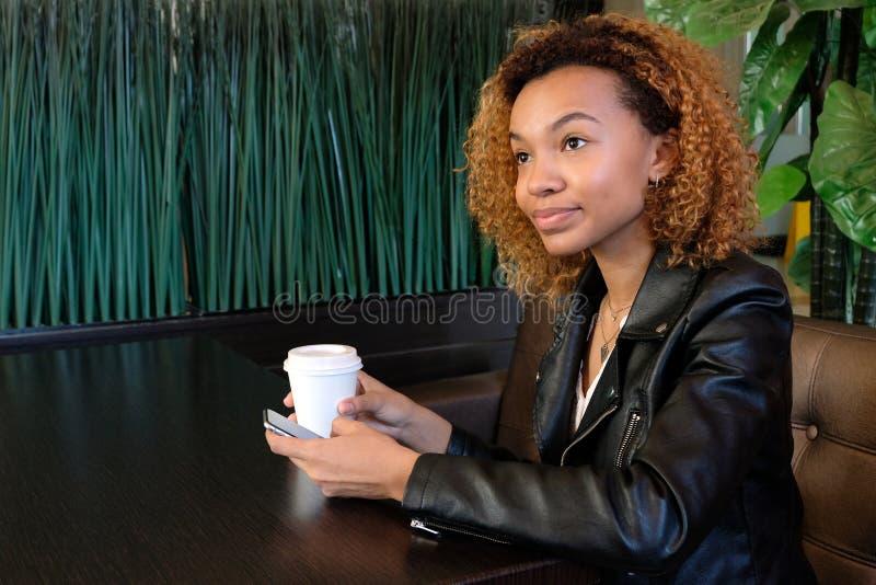 Een mooi jong zwart meisje in een leerjasje met een wit glas in één hand en een telefoon in andere, kijkt aandachtig weg royalty-vrije stock fotografie