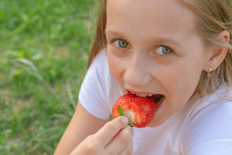 Een mooi kind met groene ogen eet aardbeien in haar handen en glimlacht stock afbeeldingen