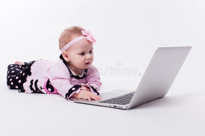 Een mooi klein babymeisje die op haar maag in een slimme speld liggen royalty-vrije stock foto
