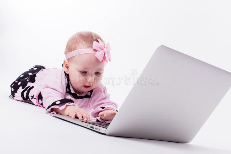 Een mooi klein babymeisje die op haar maag in een slimme speld liggen stock afbeeldingen