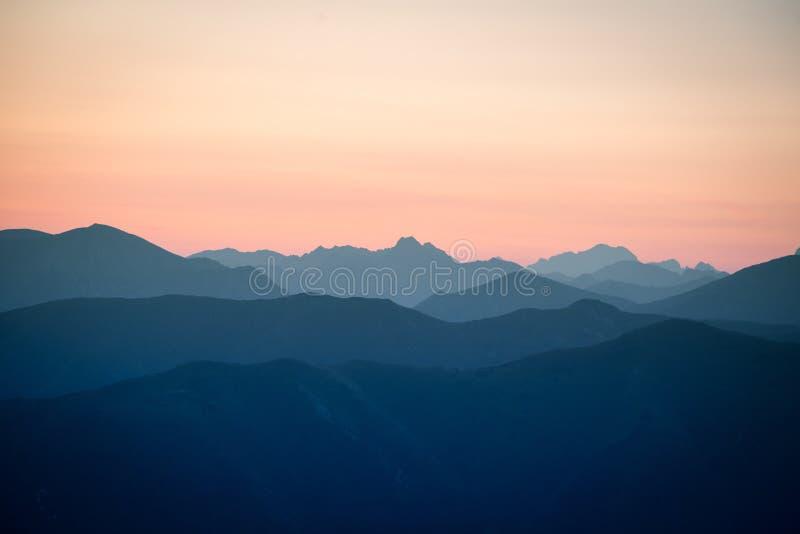 Een mooi, kleurrijk, abstract berglandschap in zonsopgang Minimalistisch landschap van bergen in ochtend in blauwe tonen stock afbeelding