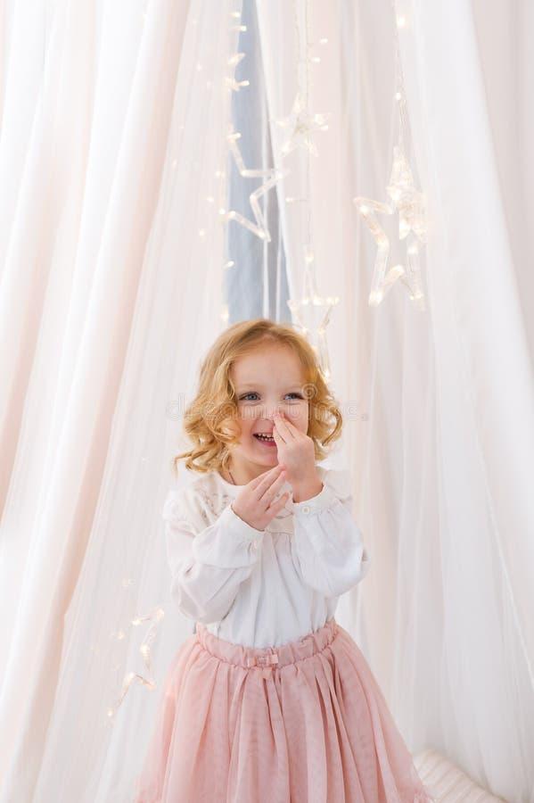 Een mooi lachend meisje bevindt zich dichtbij het witte gordijn stock afbeeldingen