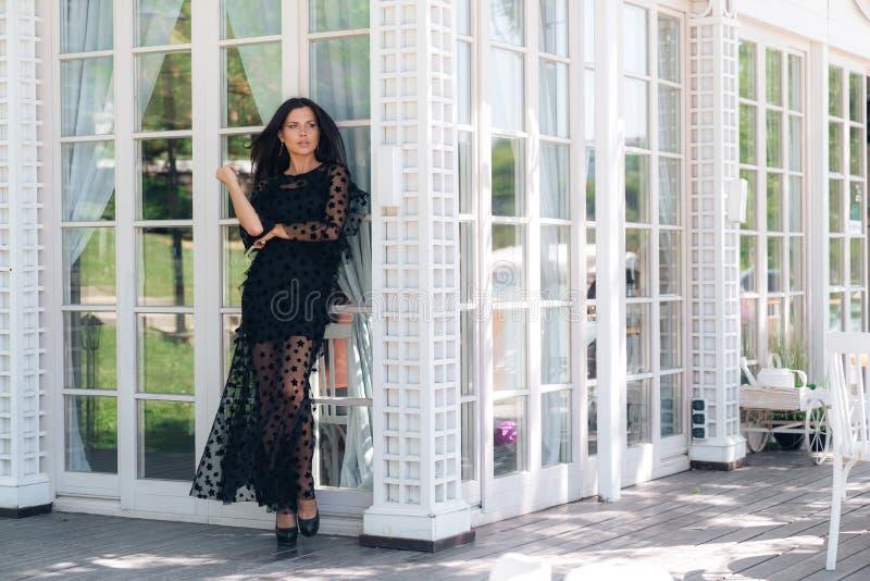 Een mooi lang brunette gekleed in een kleding van het ontwerpernetwerk bevindt zich op de glasmuur van het restaurant, spuit zijn royalty-vrije stock afbeeldingen
