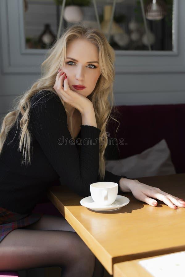 Een mooi langharig blond meisje die een minirok dragen zit en rust bij een lijst met een kop van koffie in een koffie royalty-vrije stock foto's