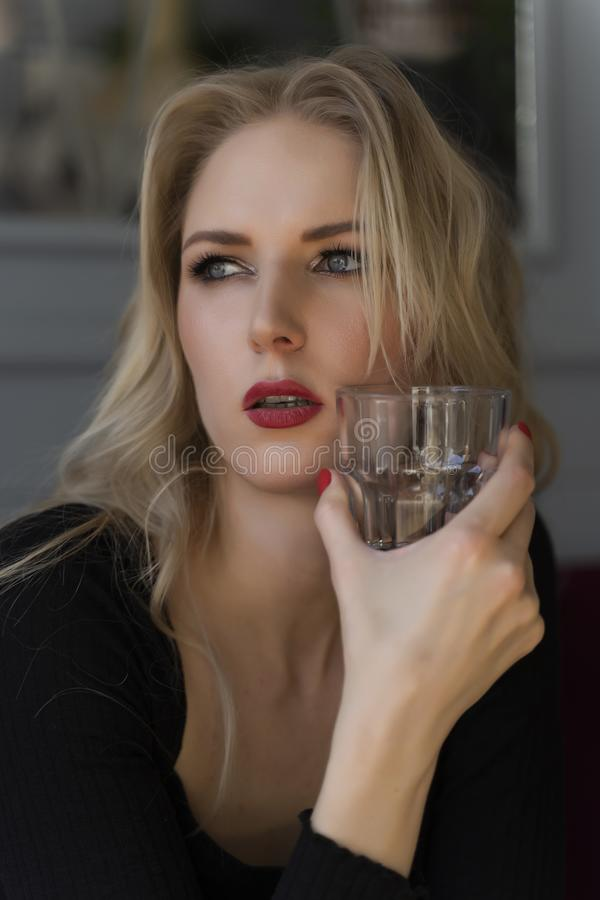 Een mooi langharig blonde zit en rust bij een lijst in een een glas van drank houden en koffie die, die uit het venster kijken royalty-vrije stock fotografie