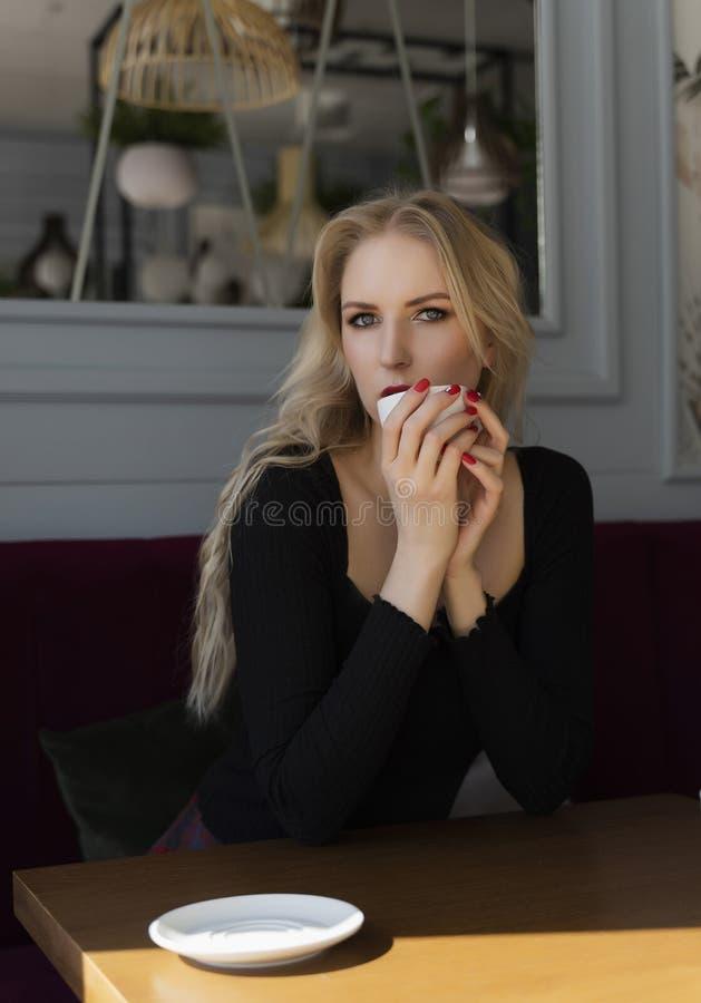Een mooi langharig blonde zit en rust bij een lijst in een een kop van koffie houden en koffie die, die uit het venster kijken royalty-vrije stock foto