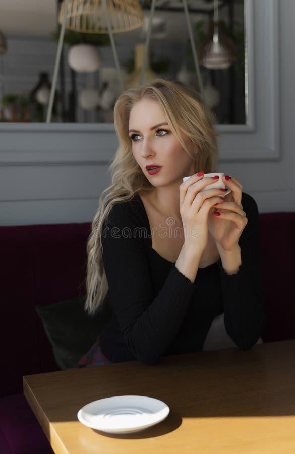 Een mooi langharig blonde zit en rust bij een lijst in een een kop van koffie houden en koffie die, die uit het venster kijken stock afbeeldingen