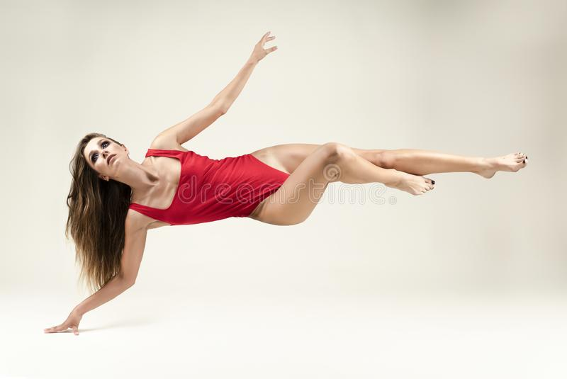 Een mooi langharig slank meisje die met lange benen een rood lichaam dragen levitatie ondergaat op een witte achtergrond, wat bet royalty-vrije stock foto