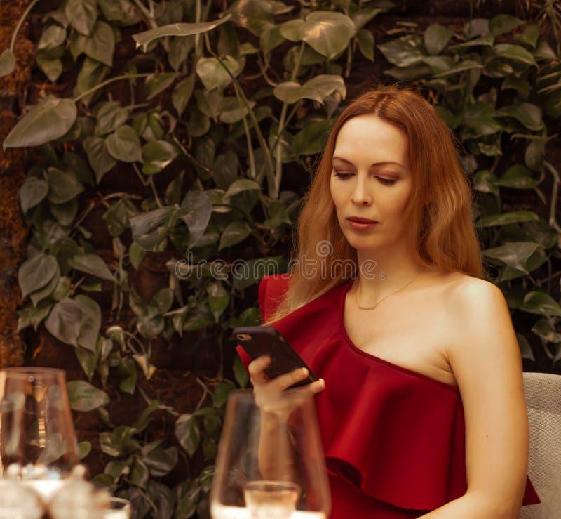 Een mooi meisje in een asymmetrische kleding op één schouder onderzoekt het telefoonscherm in een restaurant Zit alleen, het wach royalty-vrije stock afbeeldingen
