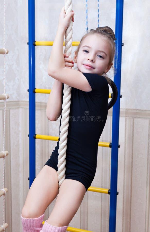 Een mooi meisje beklimt op een kabel royalty-vrije stock afbeelding