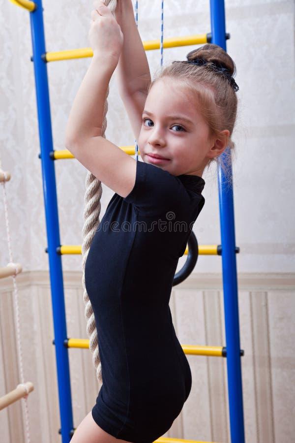 Een mooi meisje beklimt op een kabel royalty-vrije stock afbeeldingen