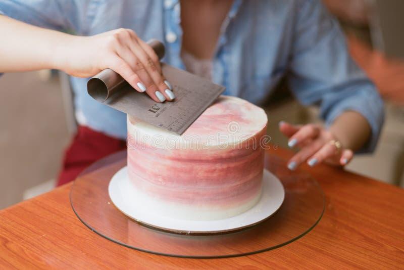 Een mooi meisje die een cake in een bakkerij maken Het meisje maakt de room op de cake glad Witte cake op een houten lijst stock afbeeldingen