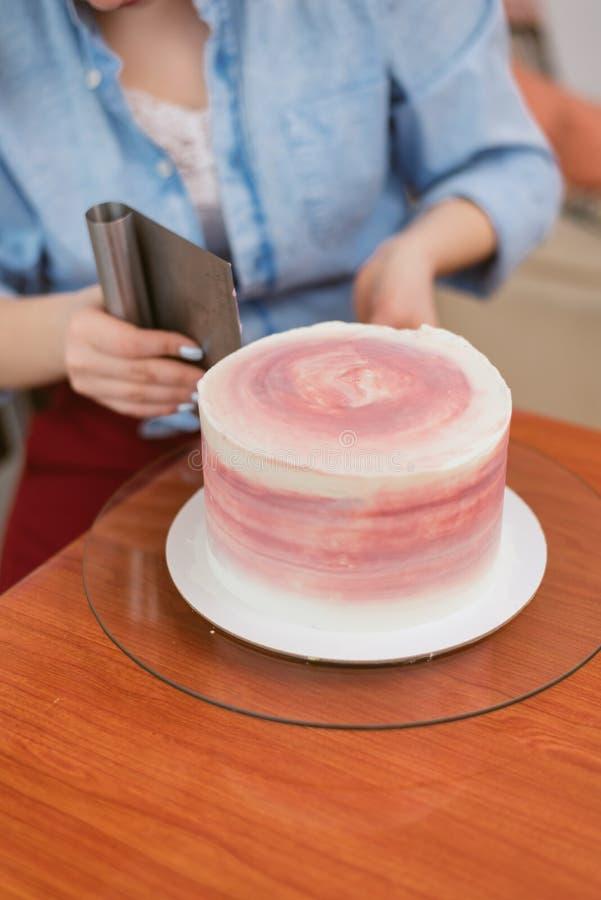 Een mooi meisje die een cake in een bakkerij maken Het meisje maakt de room op de cake glad Witte cake op een houten lijst royalty-vrije stock afbeeldingen
