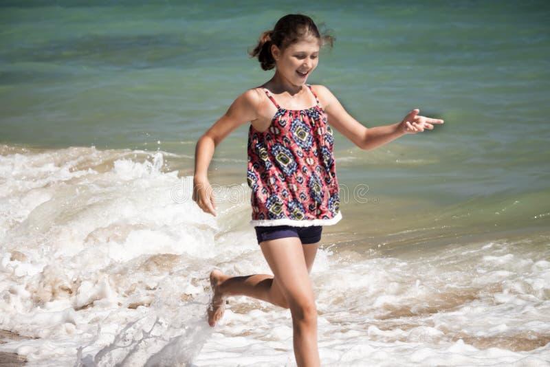 Een mooi meisje die in de golven op het vage strand lopen, de zomerconcept stock foto's