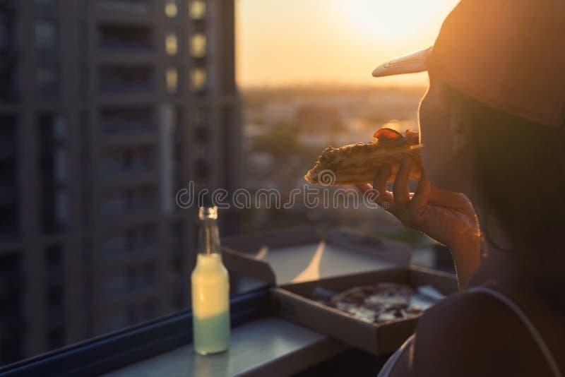 Een mooi meisje die pizza en een fles van mojito op de achtergrond van de zonsondergangstad eten stock afbeelding